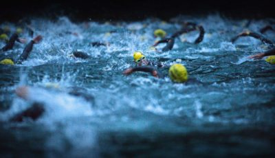EIDFJORD, NORWAY - AUGUST 03:  Athletes swim in the Hardangerfjorden during the Norseman Xtreme Triathlon on August 3, 2013 in Eodfjord, Norway. The race which was first held in 2003 runs point to point and is considered among many as the ultimate triathlon in the world. Owners and organisers Hardangervidda Triathlon Club limit the number of competitors to 250 they make their way through some of Norway's most beautiful scenery during the course of the race.  (Photo by Jeff J Mitchell/Getty Images)